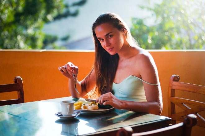 Девушка, кушающая фрукты и пьющая чай
