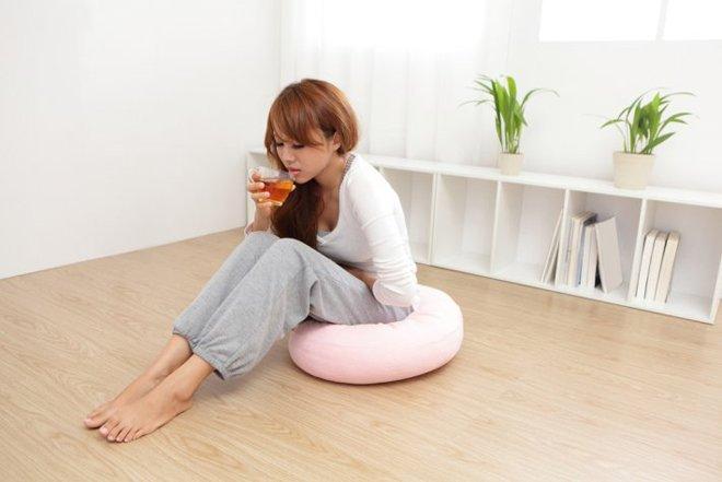 Девушка с болями в желудке пьет чай