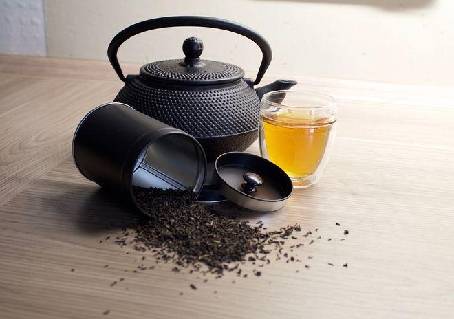Чайник и рассыпанный чай на столе